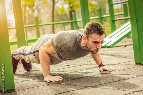 Fotografía  Push-ups - fitness man training push up outside in summer.