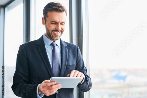 Fotografia  Happy businessman using digital tablet standing in office