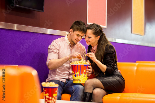 Photo  Couple on a date eating popcorn after a movie at the cinema