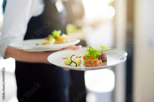 Tuinposter Restaurant Waiter carrying plates with meat dish on some festive event