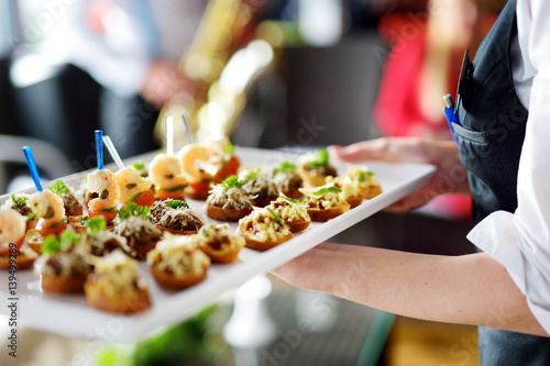Fotografia Waiter carrying plates with meat dish on festive event, party or wedding recepti