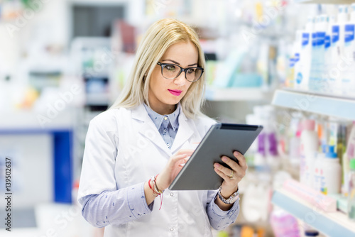 Staande foto Apotheek Pharmacy details - blonde doctor in white uniform using tablet and technology in pharmaceutical or medical field