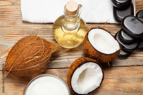 Printed kitchen splashbacks Dairy products Oil, coconut and stones for a massage on wooden background