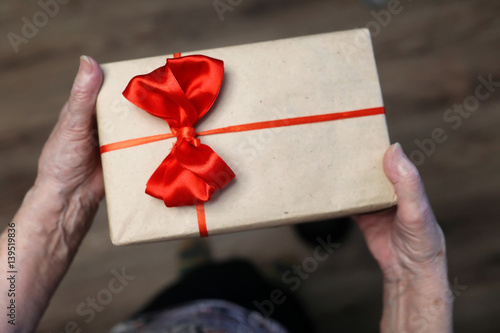 Photo  gift box with red bow in grandmother hands