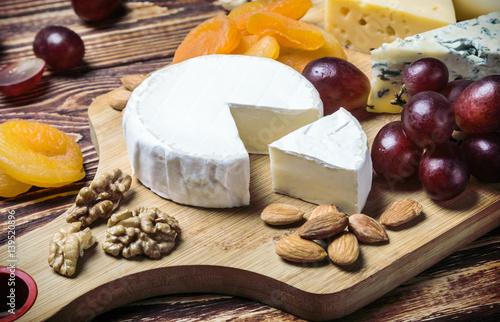 Plakat wybrane sery, orzechy i winogrona na drewnianym stole