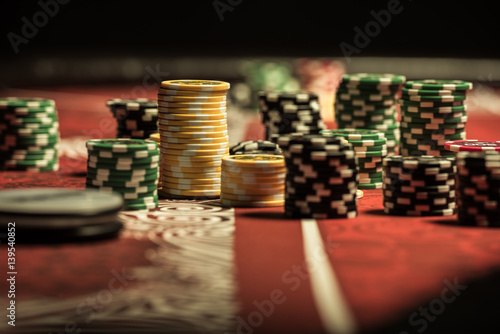 Close-up view of poker chips on poker table at casino плакат