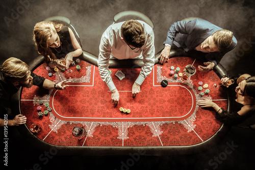 Foto  top view of men and women playing poker in casino