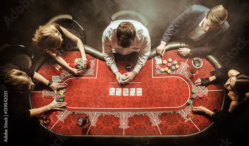 Fototapeta top view of men and women playing poker in casino obraz