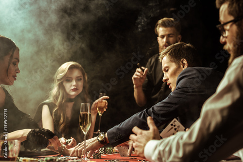 Foto  side view of concentrated men and women playing poker in casino