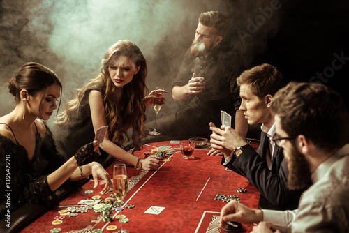 Foto  side view of people playing poker together in casino