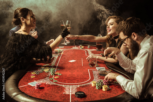 Fotografie, Obraz  side view of women clinking drinks while playing poker in casino