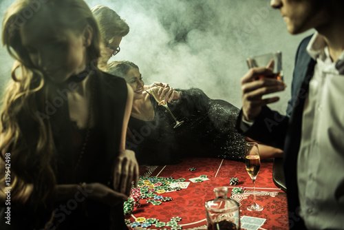 smiling woman with drink lying on poker table during game in casino плакат