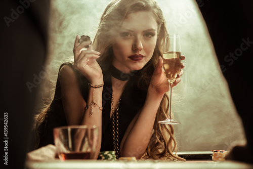 фотография  portrait of confident woman with drink and poker chip in hands
