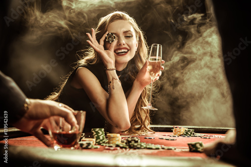 Fotografija  portrait of smiling woman with drink and poker chip playing poker