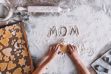 'Partial Top View Of Child Holding Heart Shaped Cookie And Word Mom Written In Flour, Mothers Day Concept