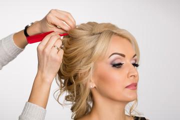 Fototapeta Hairdresser makes hair styling blond girl