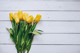 Fototapeta Tulipany - Yellow tulips bunch on white wooden planks rustic barn rural backgropund. Empty space for copy, text, lettering. Postcard, greeting card template.