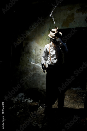 Obraz na plátně  Portrait of a gangster dressed in retro suit with hat, smoking cigar and holding gun in hands