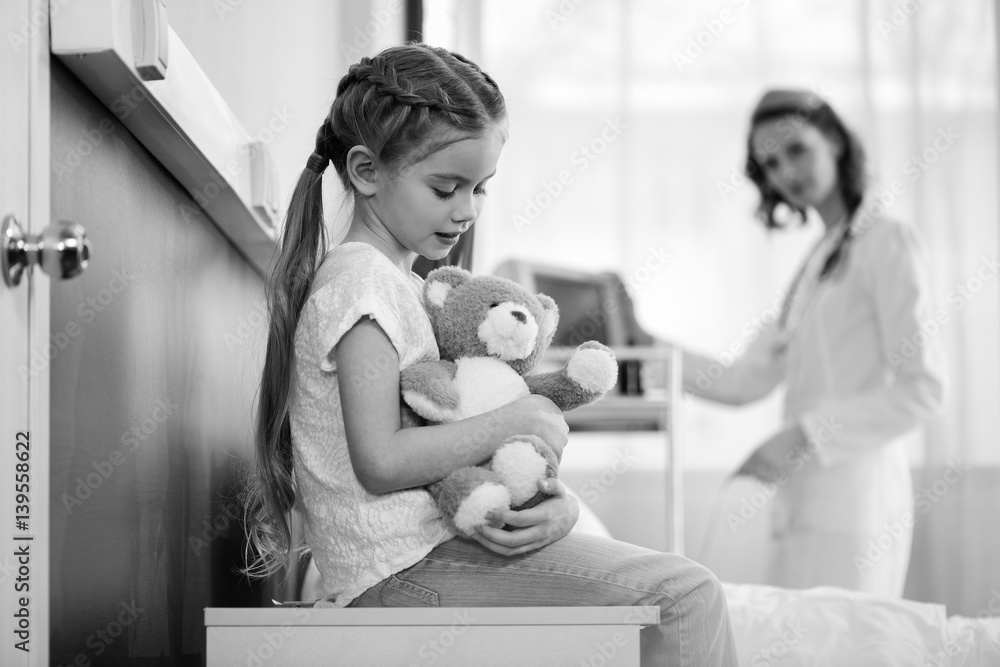 Fototapeta side view of girl with teddy bear in hospital chamber with doctor behind, black and white photo