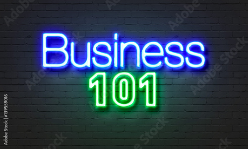 Photo Business 101 neon sign on brick wall background.