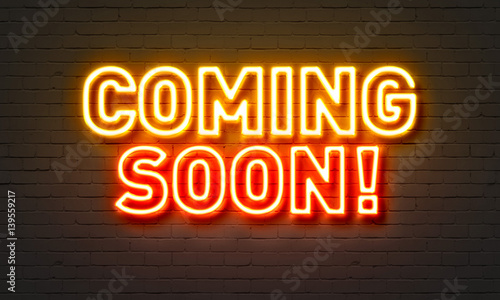 Coming soon neon sign on brick wall background. Canvas Print