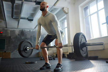 Determined athlete lifting heavy barbell
