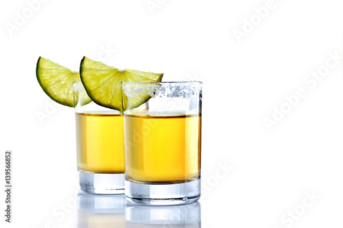 Leinwand Poster Shot of golden tequila with lime on a white background for isolation