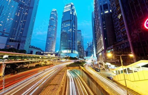 Fotografía  Nightscape of a street corner in Hong Kong with busy traffic trails at rush hour