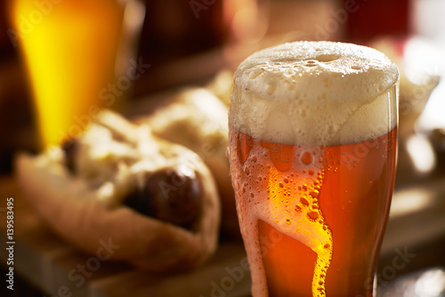 Photo  IPA beer with overflowing foamy head in mug served with bratwursts
