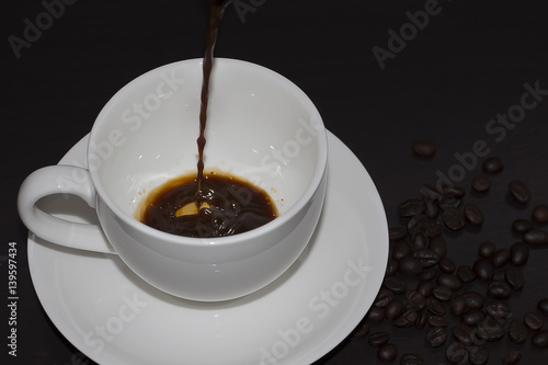 Foto op Canvas Chocolade Pour hot coffee into a cup of white on a dark background.