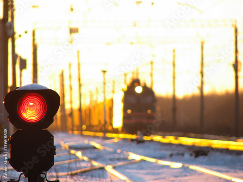 Railway traffic light shows blue signal on railway with blur effect and railway with freight train as the background during sunset.