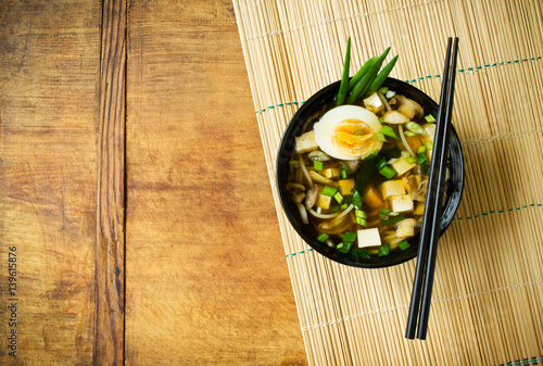 Asian soup in bowl on bamboo mat with copy space Canvas Print
