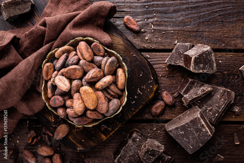 Fotomural Cocoa beans and chocolate on wooden background