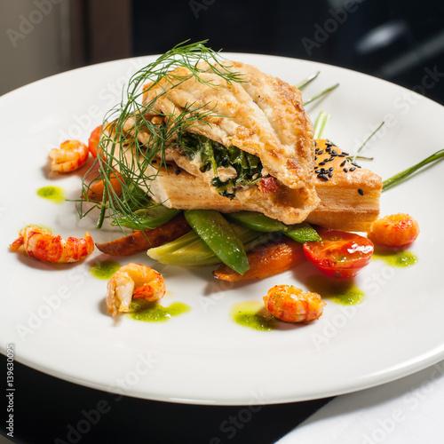 Obraz na plátne Roasted flounder stuffed with spinach and cauliflower salad, crayfish tales