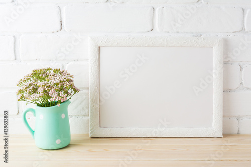Fotografiet  White landscape frame mockup with soft pink flowers in pitcher