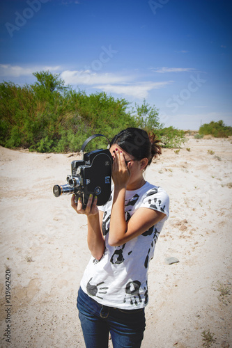 Fotografie, Obraz  Girl Shooting 16mm Film Camera in Desert