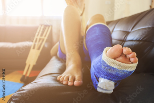Fotografía  broken leg in a plaster cast with soft-focus in the background