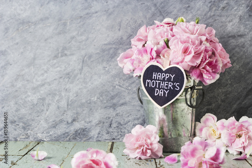 Pink carnation flowers in zinc bucket with happy mothers day letter on wood heart