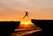 Courage Man Jumping Over Cliff On Sunset Background,Business Concept Idea