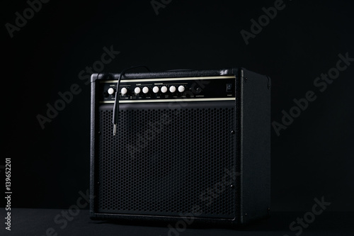 Black guitar amplifier with jack cable on black background. Canvas Print