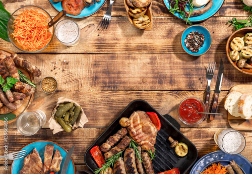 Spoed Foto op Canvas Grill / Barbecue Barbecued steak, sausages and grilled vegetables on wooden picnic table