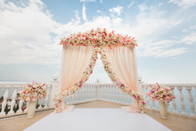 Wedding Arch Peach Color With Flowers On The Background Of The Sea. Vases With Fresh Flowers.