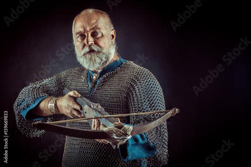 Foto Tempelritter, der mit Armbrust aufwirft. Dunkler Hintergrund.