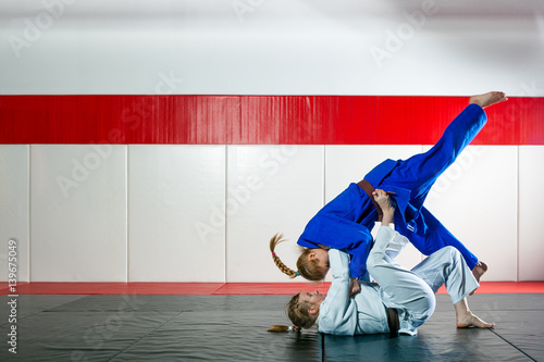 Photo  Two women fight judo on tatami