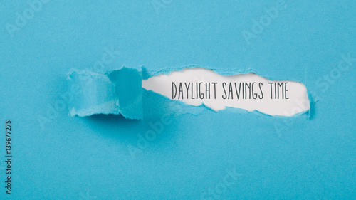Foto  Daylight Saving Time on paper torn ripped opening