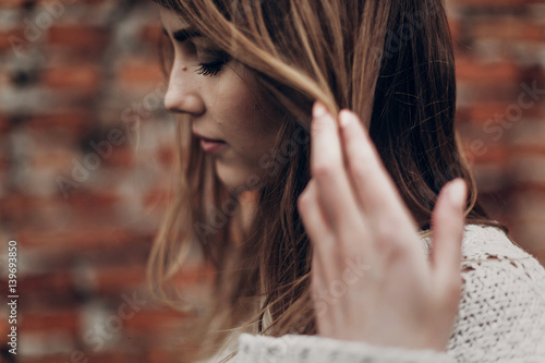 Fotomural stylish hipster gypsy woman posing in knitted sweater on background of brick wall, holding hair