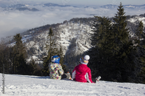 Valokuva  Two little girls skiers sitting in the snow