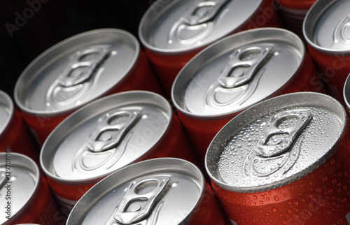 a group of red tin cans with water droplets closeup on a black background Fotobehang
