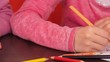 Children paint pencils. Two little girls draw on paper with crayons. Two sisters at home, on an orange couch draw on the table.