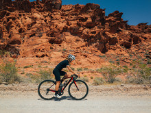 Cute Female Cyclist Riding Near Sand Rocks In Nevada Desert In The Summer